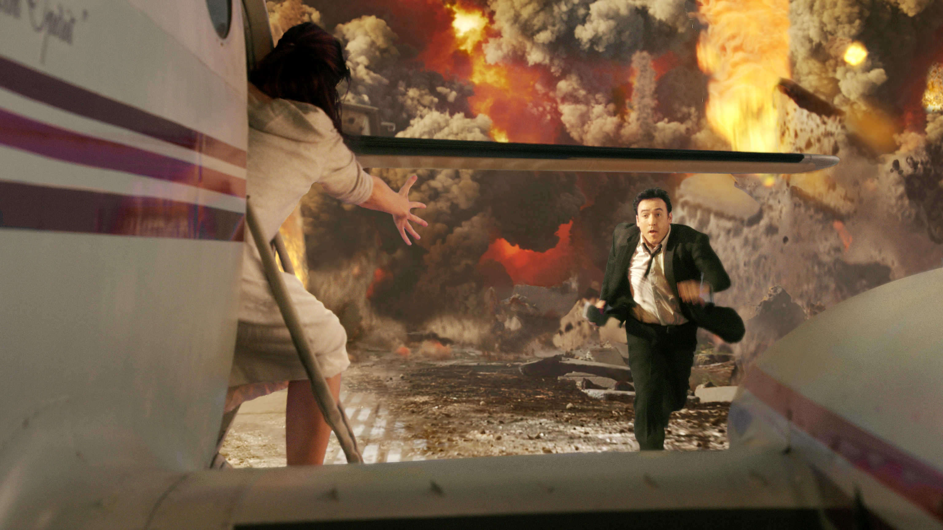 John Cusack races to get to a departing plane as Yellowstone erupts in 2012 (2009)