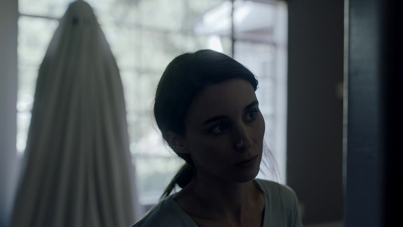 The ghost of C (Casey Affleck) hovers invisibly behind his widow M (Rooney Mara) in A Ghost Story (2017)