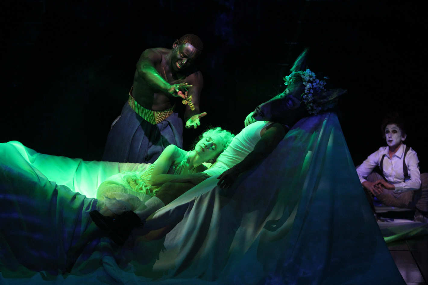 King Oberon (David Harewood) comes across his wife Titania (Tina Benko) curled in the arms of the actor Bottom (Max Casella) who was been transformed into a donkey, while the knave Puck (Kathryn Hunter) looks on in A Midsummer Night's Dream (2014)
