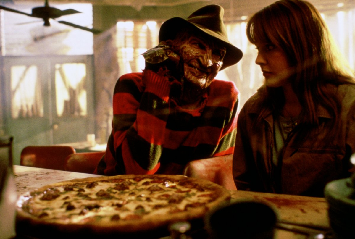 Freddy Krueger (Robert Englund) sits down to enjoy a pizza with Alice Johnson (Lisa Wilcox) in A Nightmare on Elm Street IV: The Dream Master (1988)