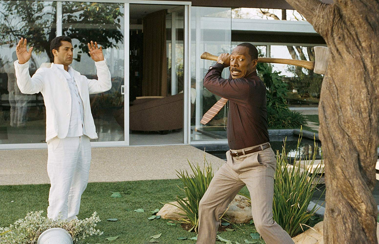 Guru Cliff Curtis looks on as Eddie Murphy goes to attack the tree with an axe in A Thousand Words (2012)