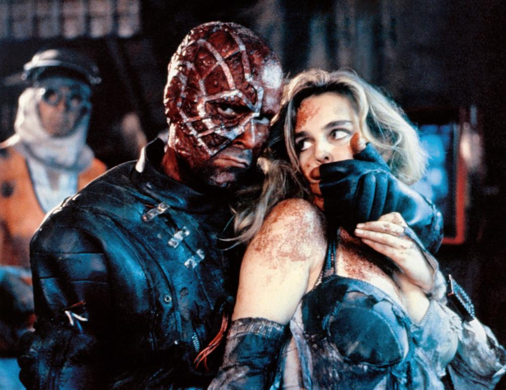 Mutant terrorist leader Ramon Yrritu (Antonio Resines) with his hostage heiress Frederique Feder in Accion Mutante (1993)