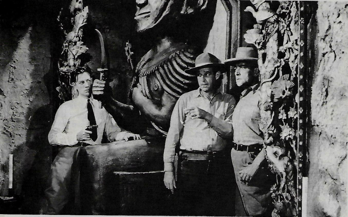 Flyer hero Ace Drummond (John 'Dusty' King) waits to ambush two villains as they enter a temple in Ace Drummond (1936)