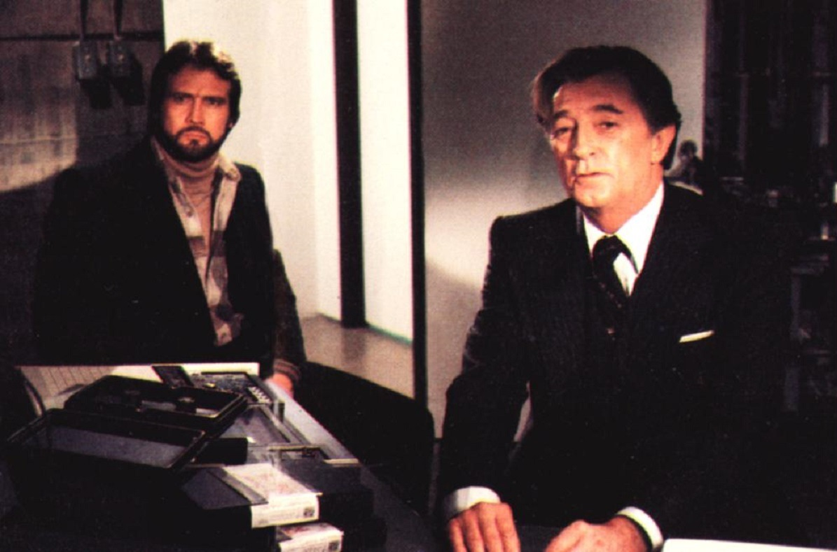 (l to r) Lee Majors as the advertising agency creative director who uncovers a conspiracy and the agency's director Robert Mitchum in Agency (1979)