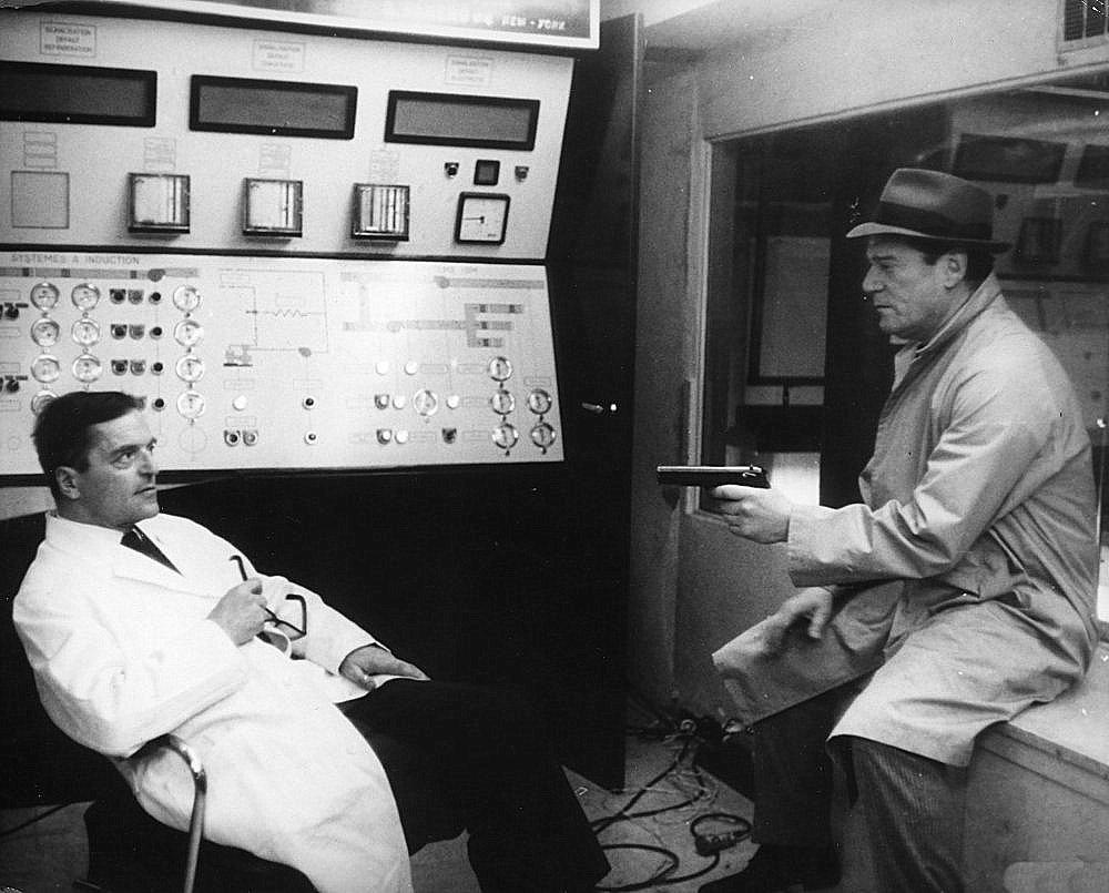 Lemmy Caution (Eddie Constantine) holds Professor Von Braun (Howard Vernon) at gunpoint in Alphaville (1965)