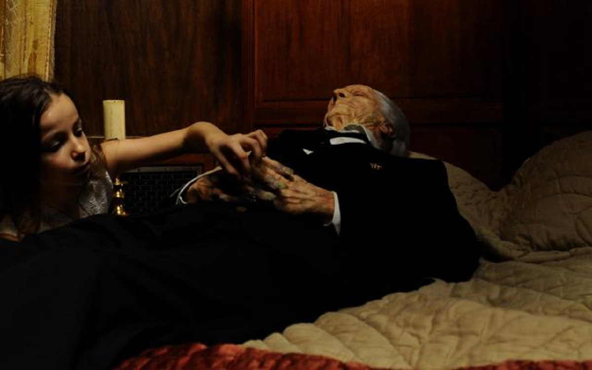 Young Ana (Cassandra Foret) tries to take the pocket watch from the corpse of her grandmother in the first episode of Amer (2009)