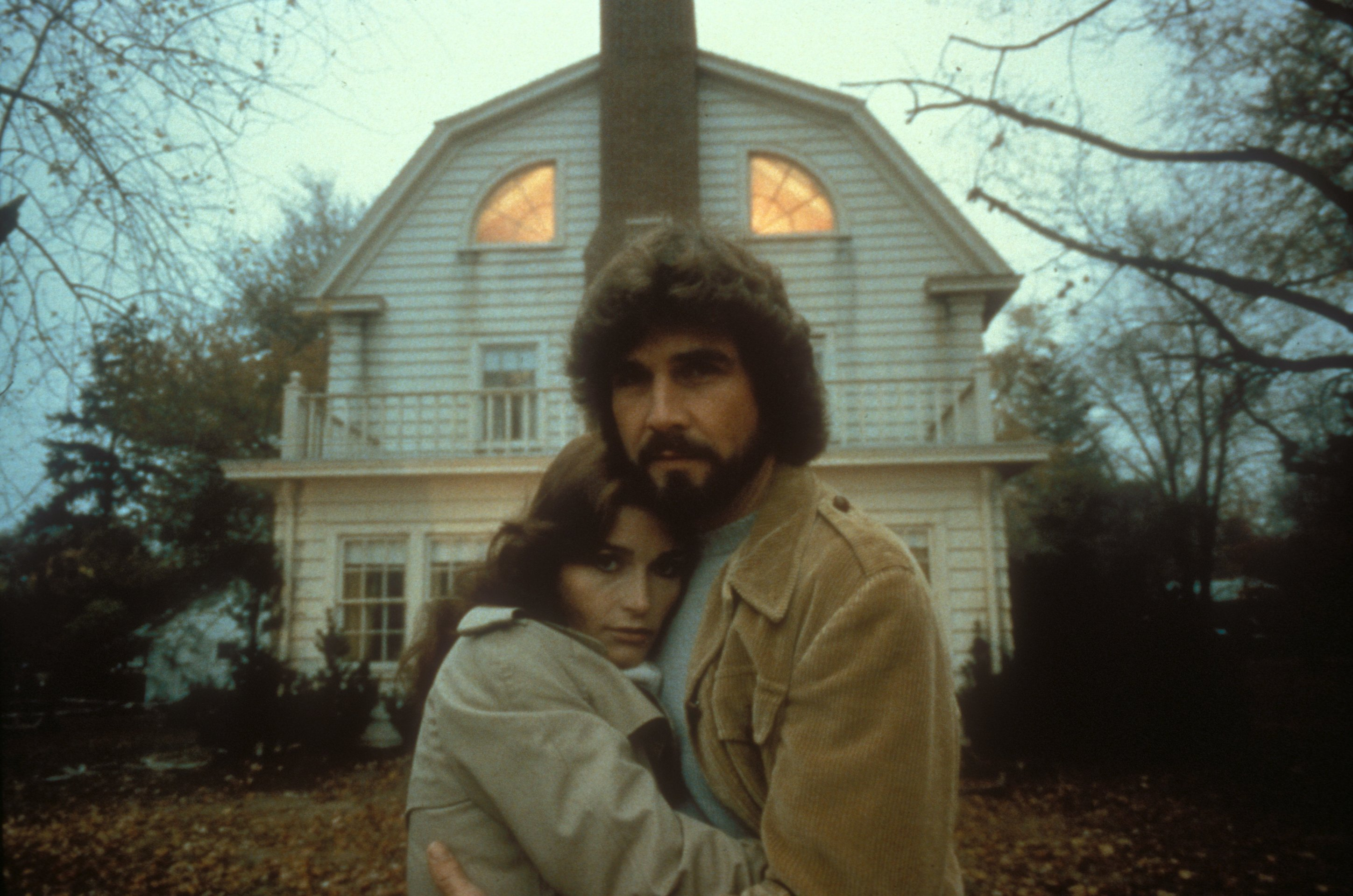 George and Kathy Lutz (James Brolin and Margot Kidder) stand in front of the Amityville house