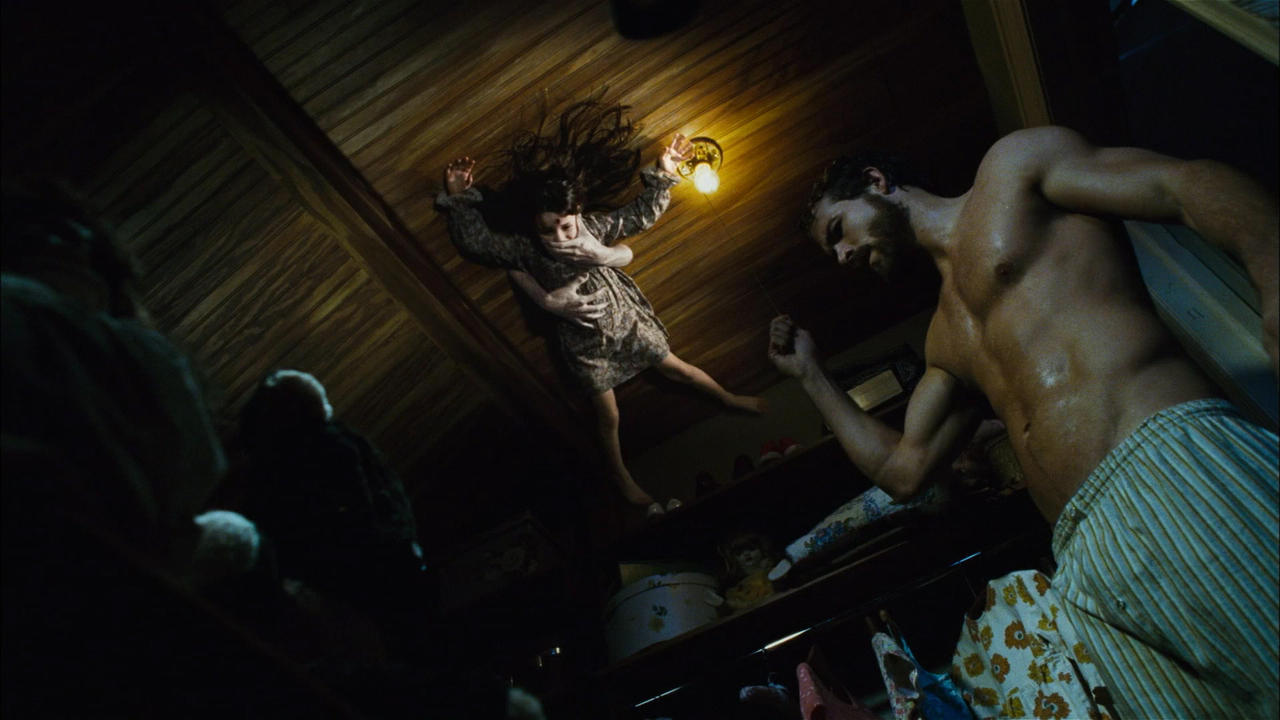 Ryan Reynolds enters the room while supernatural forces pin Chloe Grace Moretz to the roof in The Amityville Horror (2005)