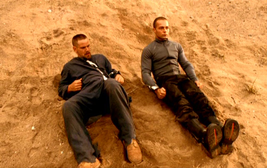 (l to r) Human Scott Bairstow and android Joseph Lawrence chained together in the desert in Android Apocalypse (2006)