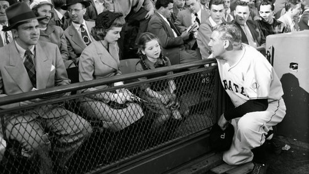 Coach Paul Douglas stops on the sideline to talk to young Donna Corcoran who claims to see angels. With reporter Janet Leigh to her left in Angels in the Outfield (1951)