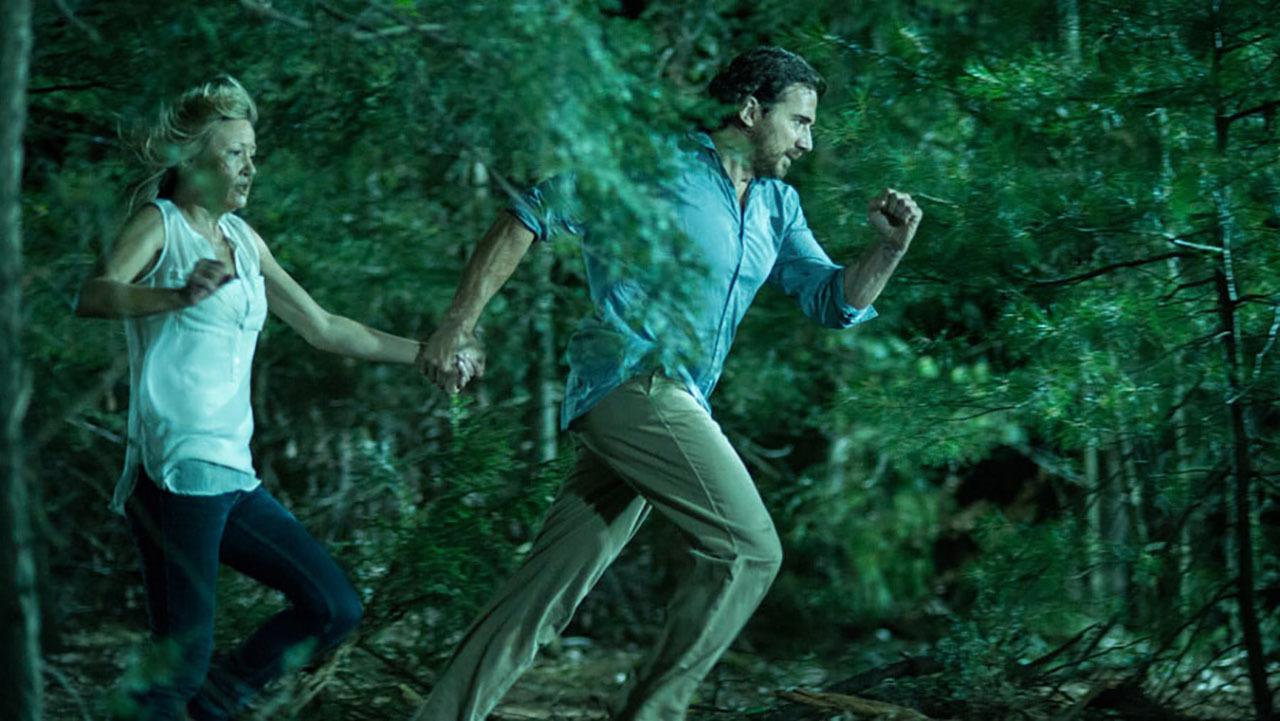 Joey Lauren Adams and Thorsten Kaye flee from the creature in Animal (2014)