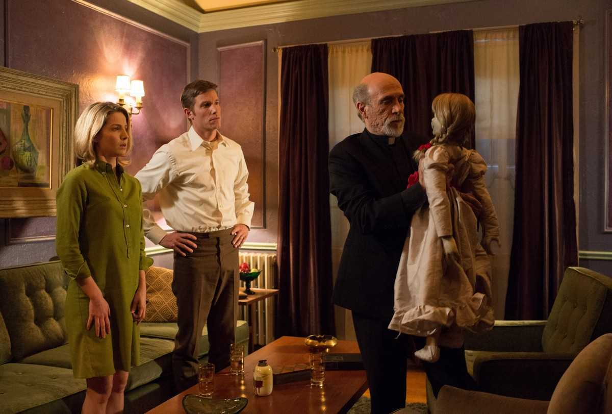 Husband and wife Annabelle Wallis and Ward Horton look on as priest Tony Amendola attempts to exorcise  the doll in Annabelle (2004)