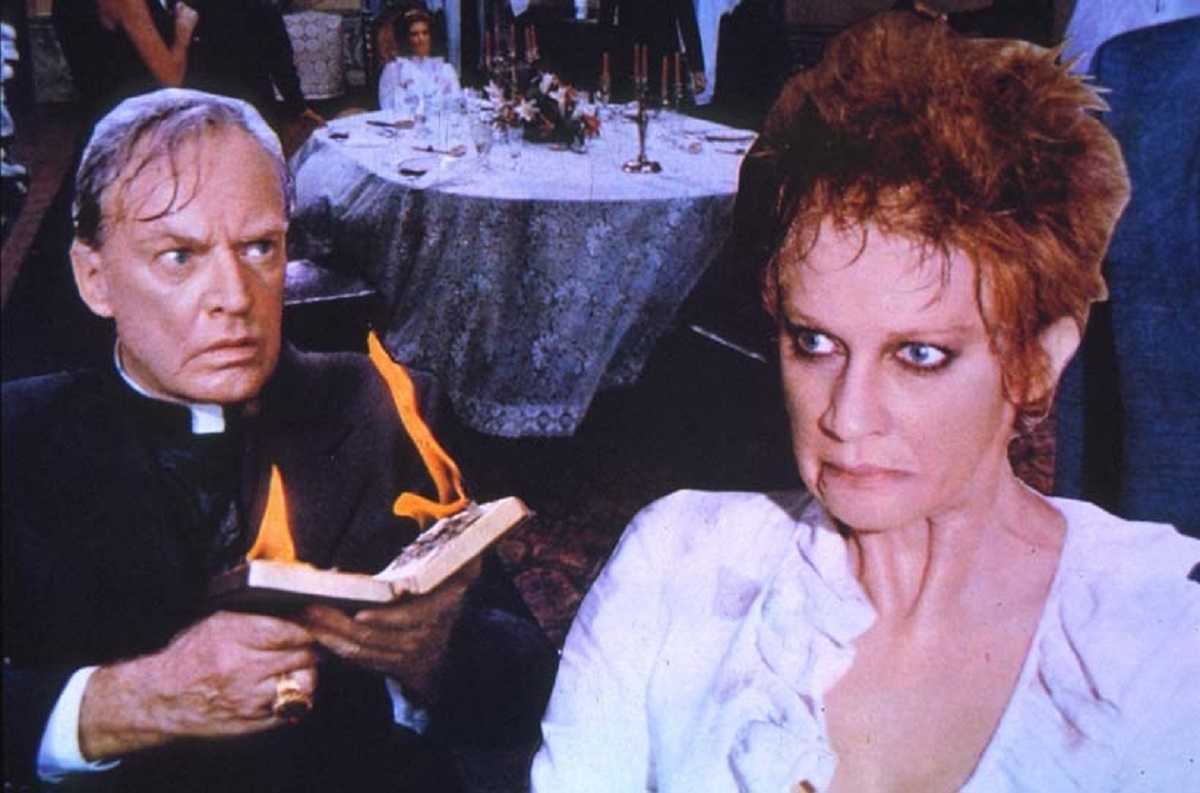 Priest Arthur Kennedy's Bible bursts into flames as he tries to exorcise Carla Gravina in The Antichrist (1974)