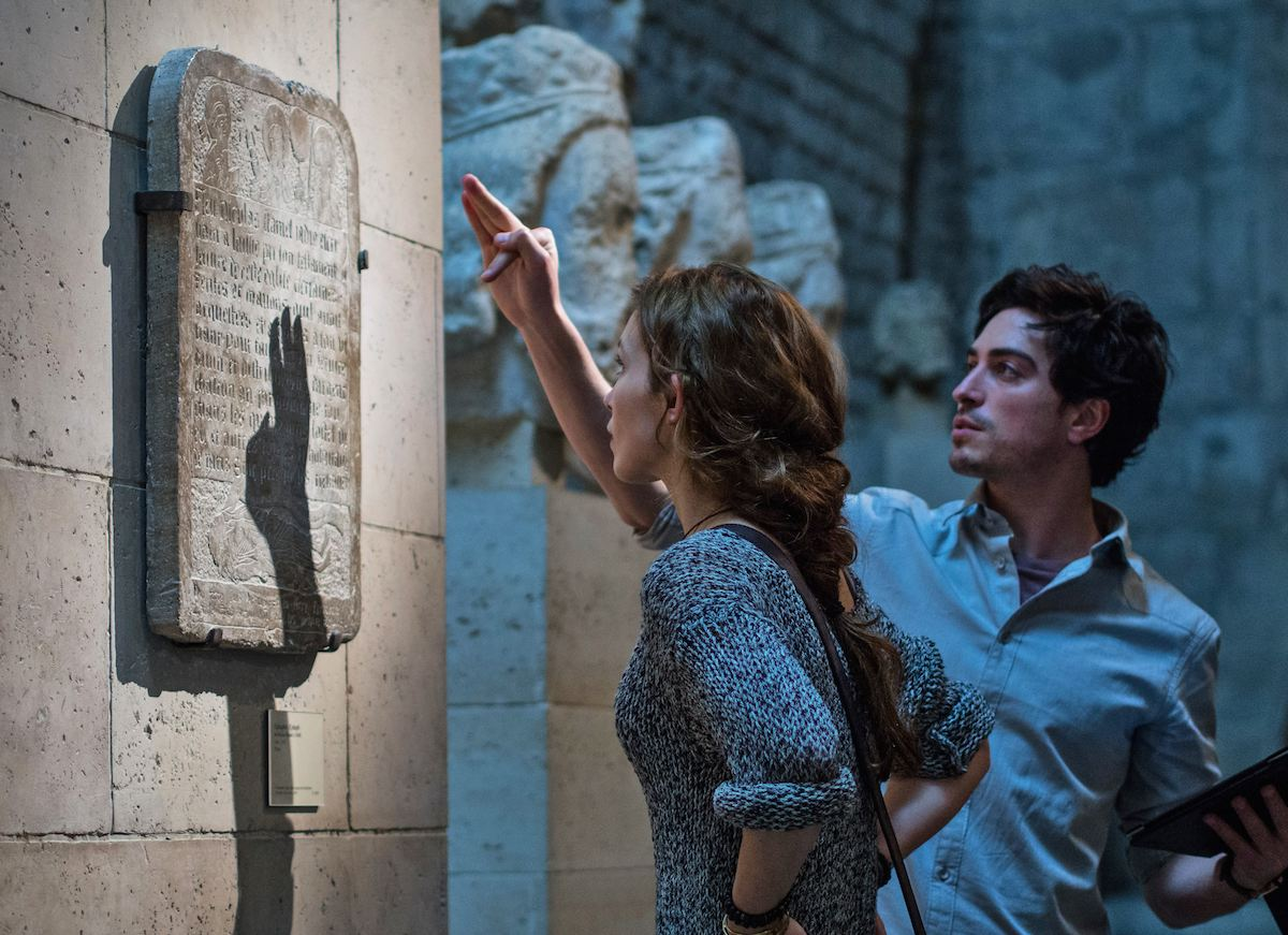 Perdita Weeks and Ben Feldman find a plaque leading to the entrance of the catacombs in As Above, So Below (2014)
