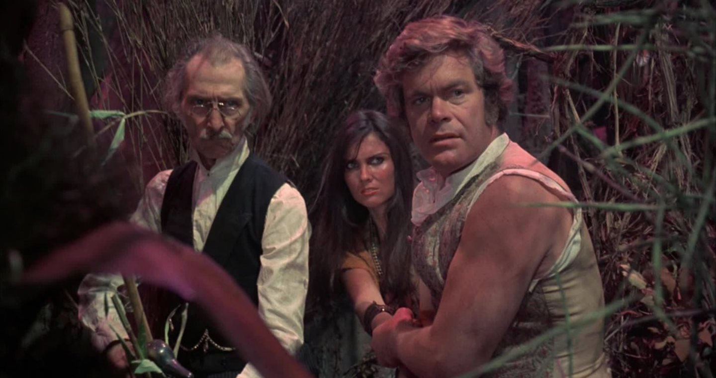 Dr Abner Perry (Peter Cushing), native girl Princess Dia (Caroline Munro) and David Innes (Doug McClure) in At the Earth's Core (1976)
