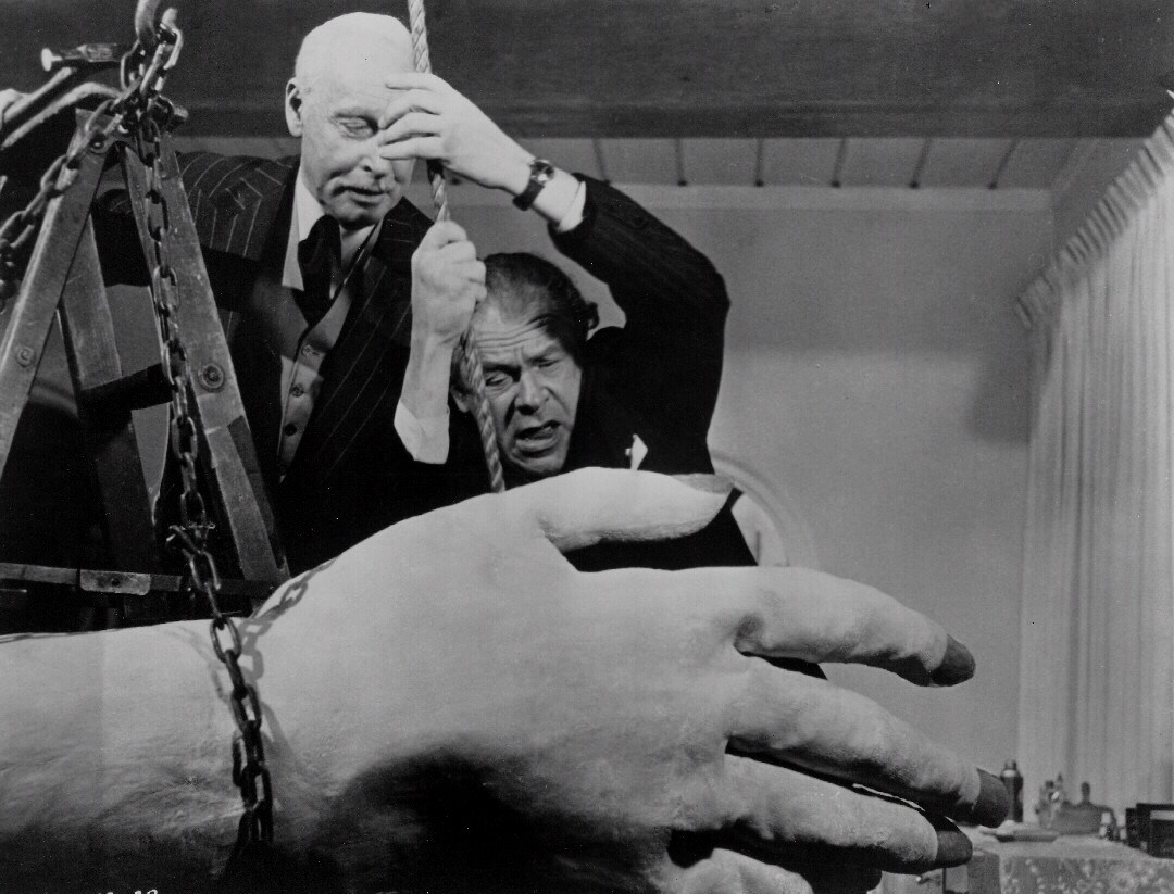 The authorities attempt to restrain the 50 Foot Woman's papier-mache hand in Attack of the 50 Foot Woman (1958)