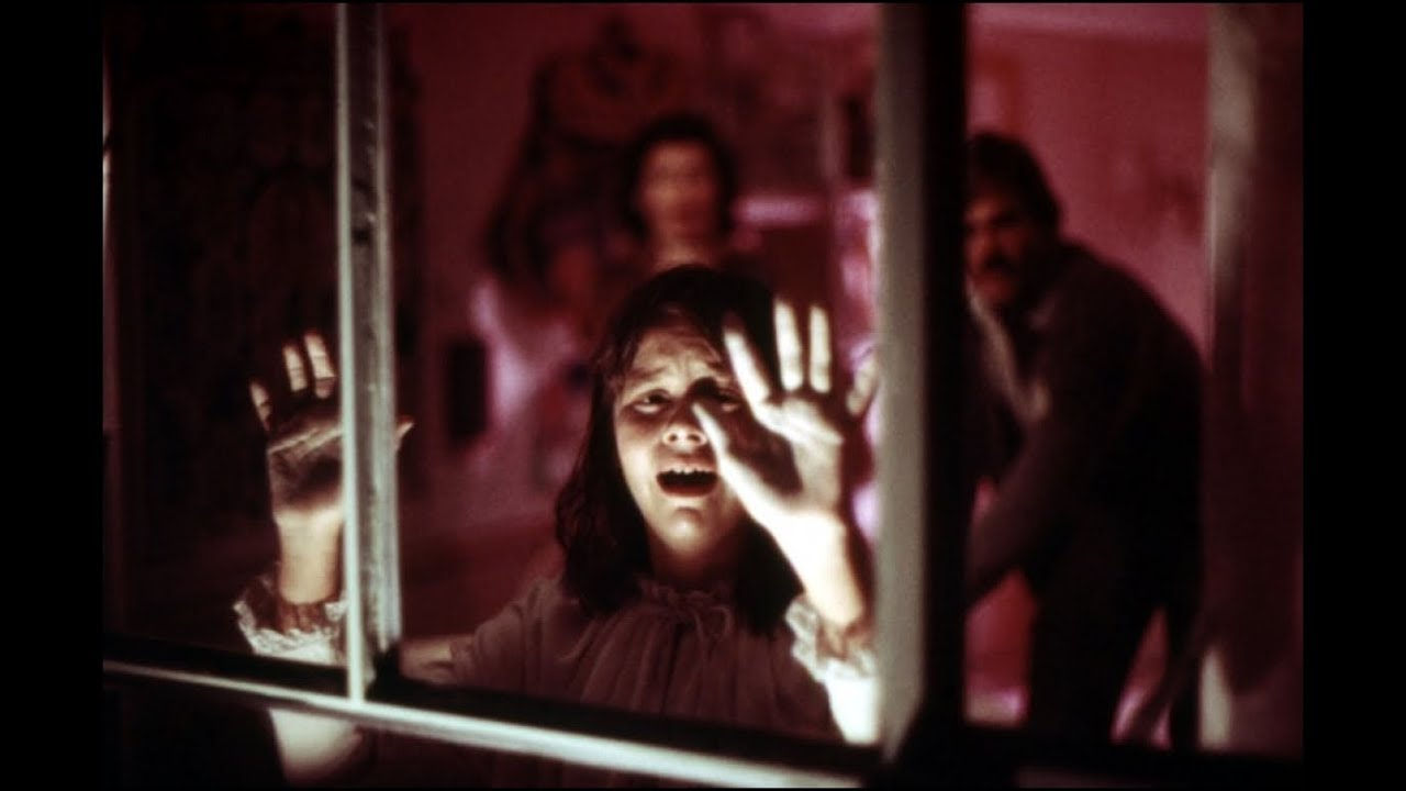 A terrified Ivy Templeton (Susan Swift) with parents Marsha Mason and John Beck (out of focus in background) in Audrey Rose (1977)