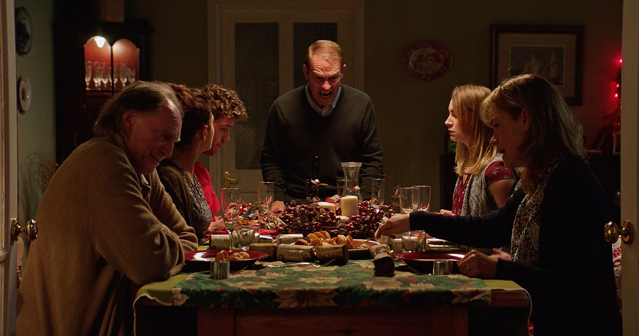 Sitting down to family dinner - (clockwise from left) Grandad David Bradley, the girlfriend Neerja Naik, son Sam Gittins, father Grant Masters, daughter Holly Weston and wife Abigail Cruttenden in Await Further Instructions (2018)