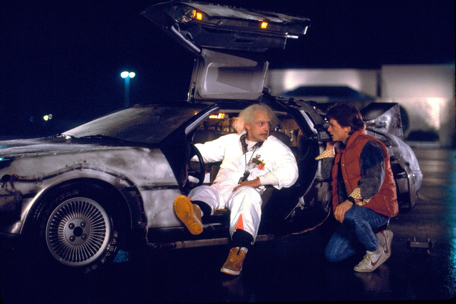 Doc Brown (Christopher Lloyd) and Marty McFly (Michael J. Fox) with the DeLorean in Back to the Future (1985)