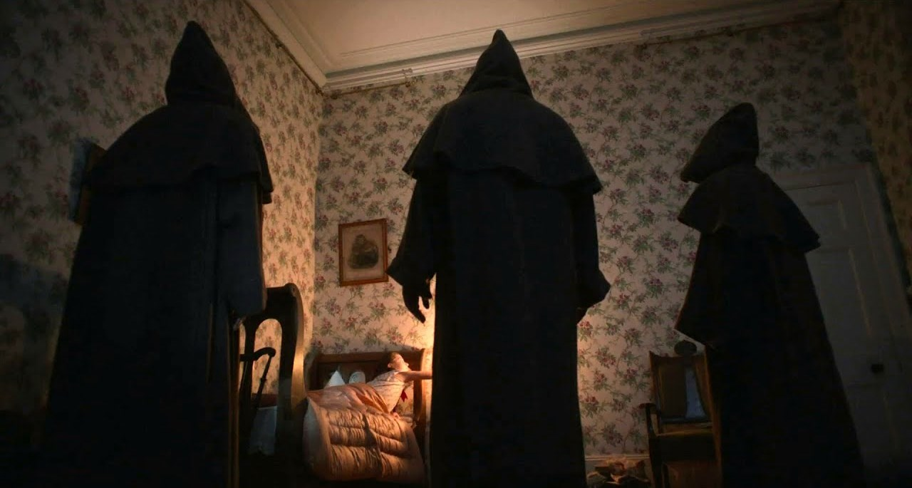 Young Anya McKenna-Bruce surrounded by hooded figures in The Banishing (2020)