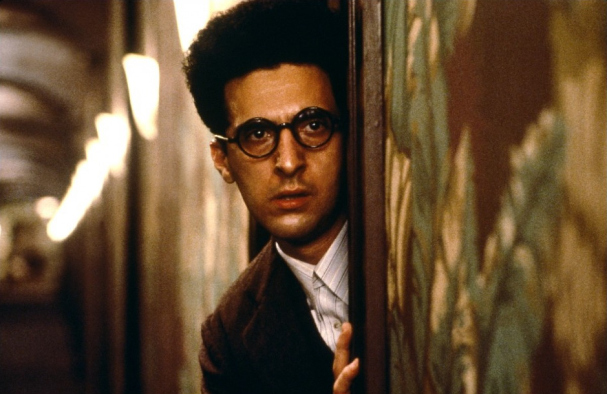 John Turturro as Barton Fink looks out his hotel door
