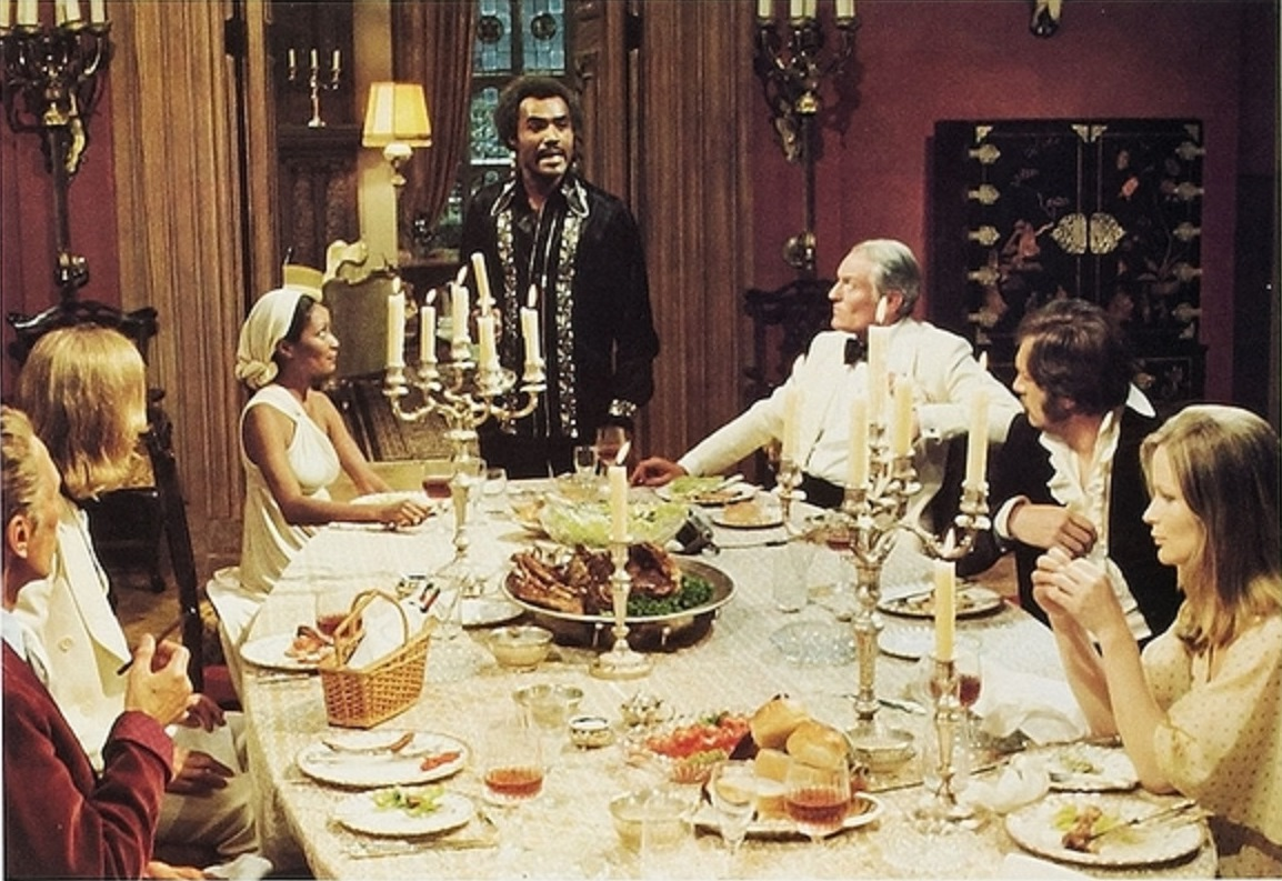The gathered guests - (clockwise from left) Peter Cushing, Tom Chadbon, Marlene Clark, Calvin Lockhart, Charles Gray, Michael Gambon and Ciaran Madden in The Beast Must Die (1974)