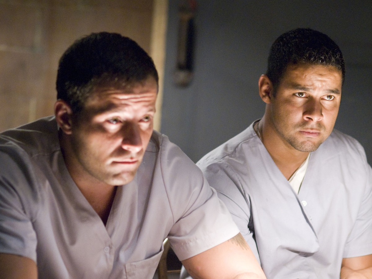 Abducted paramedics Johnny Messner, Jon Huertas in Believers (2007)