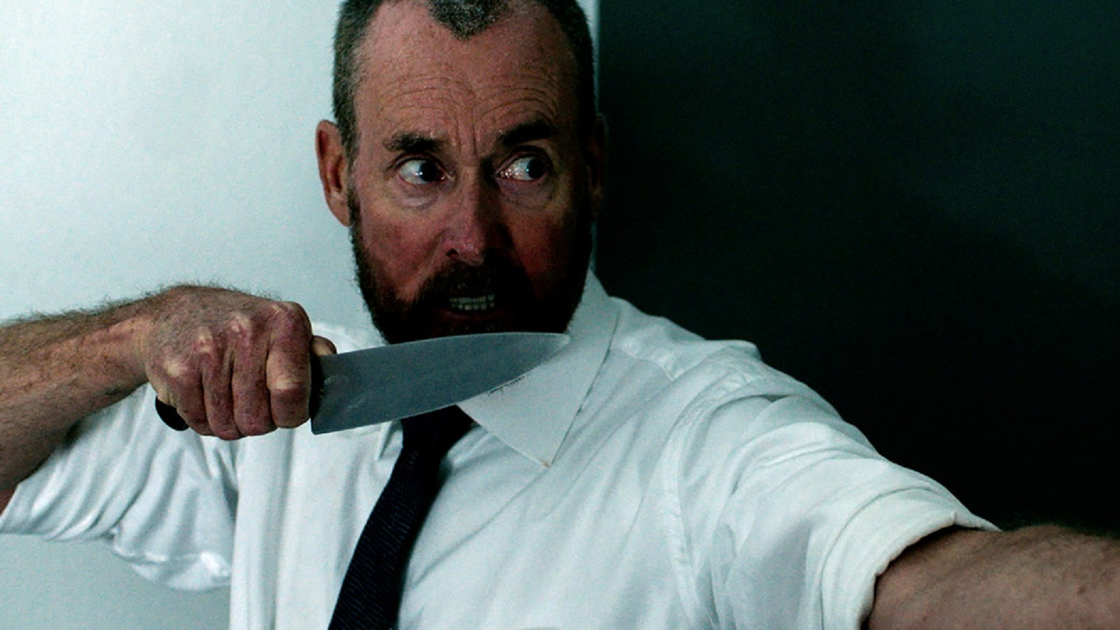 John C. McGinley moves through the office armed with knife in The Belko Experiment (2016)