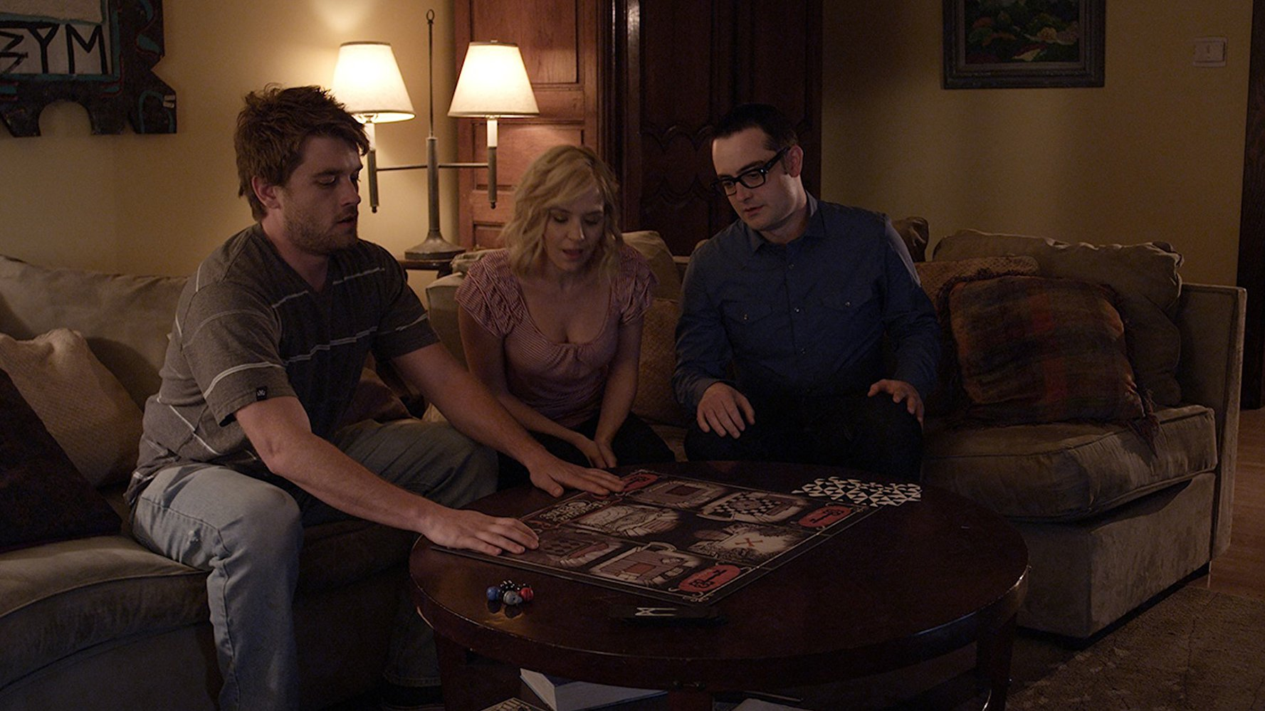 Brothers Chase Williamson and Graham Skipper with the latter's girlfriend Brea Grant sit down to play the video boardgame in Beyond the Gates (2016)