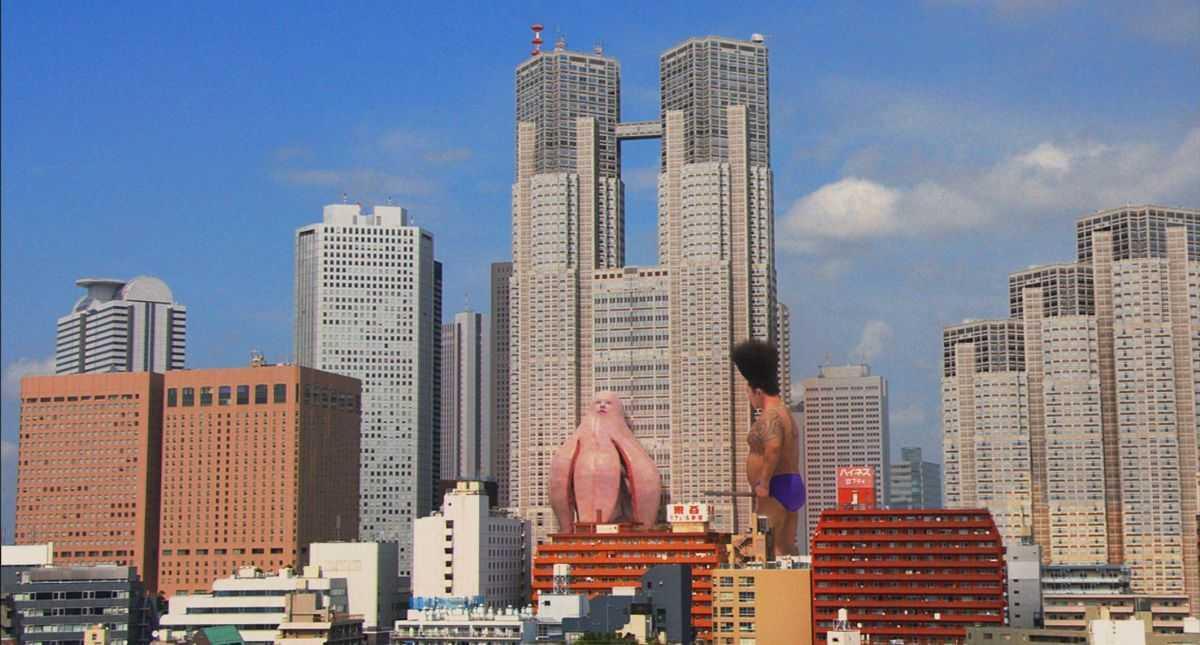 Big Man Japan (Hitoshi Matsumoto) faces off against a monster in Big Man Japan (2007)