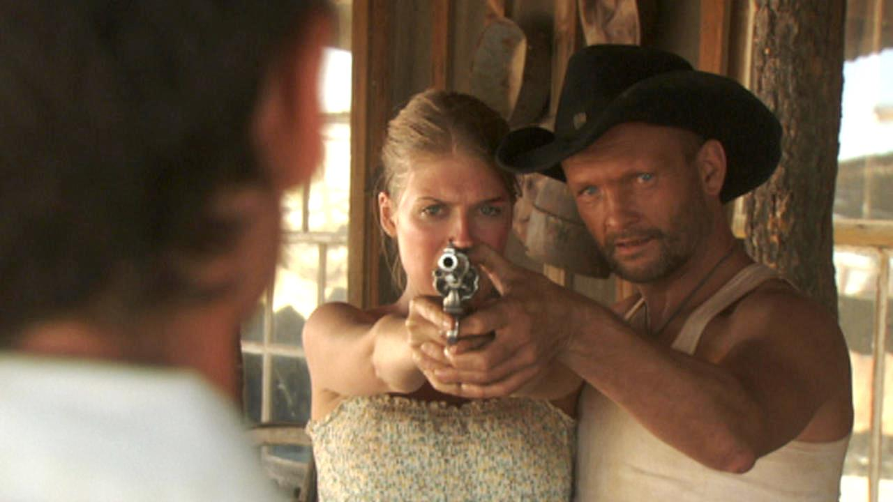 Andrew Howard shows Tess Panzer how to aim a gun in Blood River (2009)