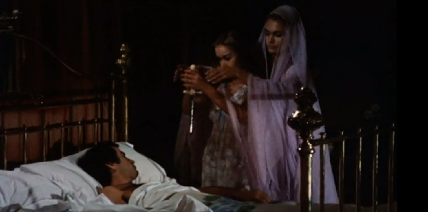Husband Simon Andreu sleeps as wifw Maribel Martin is urged to castrate him by Carmilla (Alexandra Bastedo) in The Blood Spattered Bride (1972)