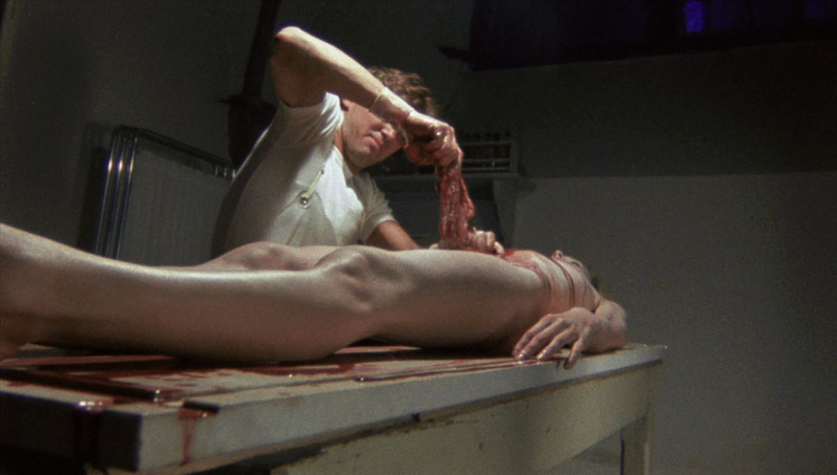 Kieran Canter removes the viscera from Cinzia Monreale's corpse in Blue Holocaust (1979)