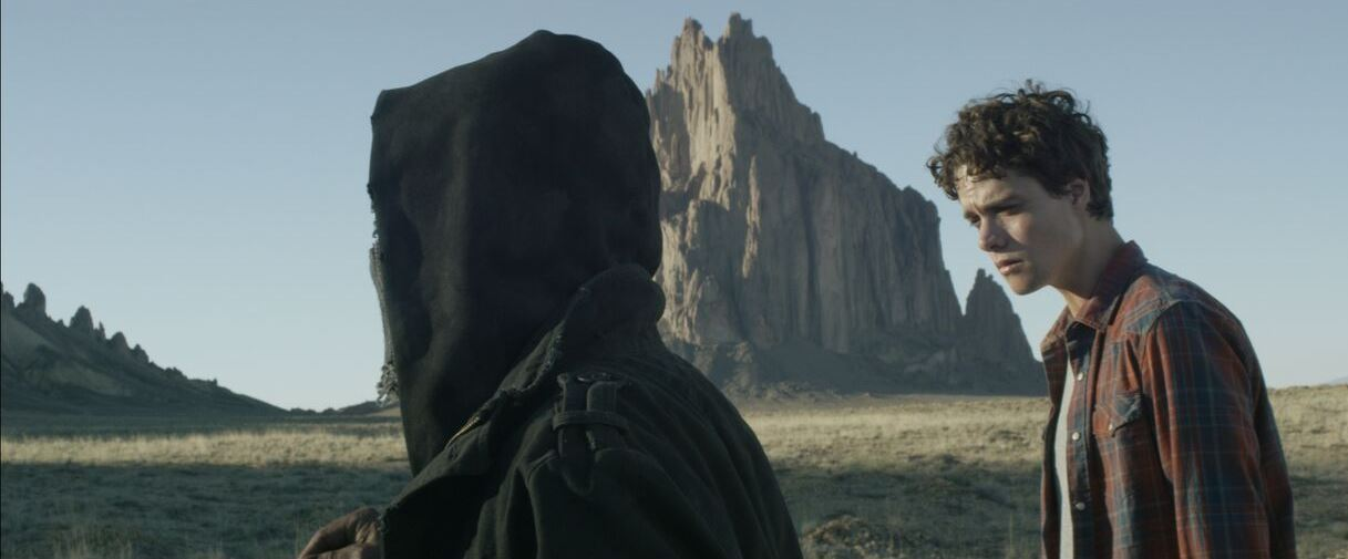 Douglas Smith is taken to an unmarked grave site in the desert by a mysterious hooded figure in Bottom of the World (2017)