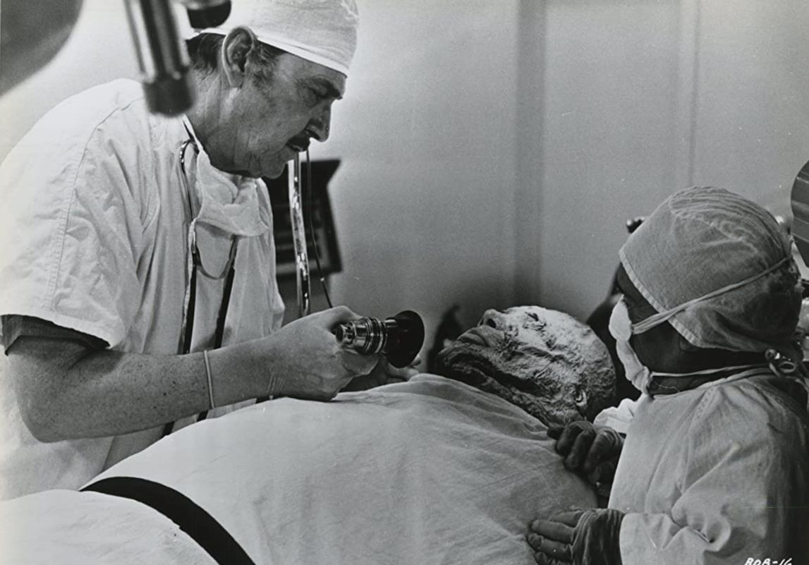 Dr Lloyd Trenton (Kent Taylor) aided by dwarf lab assistant Dorro (Angelo Rossitto) prepares to remove the brain of Abdul Amir in Brain of Blood (1971)