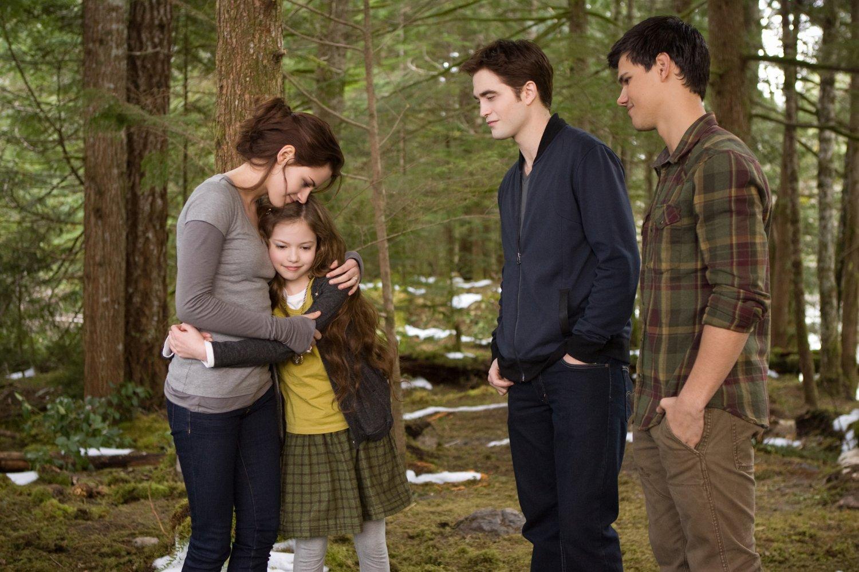 Bella Swan (Kirsten Stewart) and daughter Renesmee (Mackenzie Foy) as Edward Cullen (Robert Pattinson) and Jacob Black (Taylor Lautner) look on inBreaking Dawn Part Two (2012)