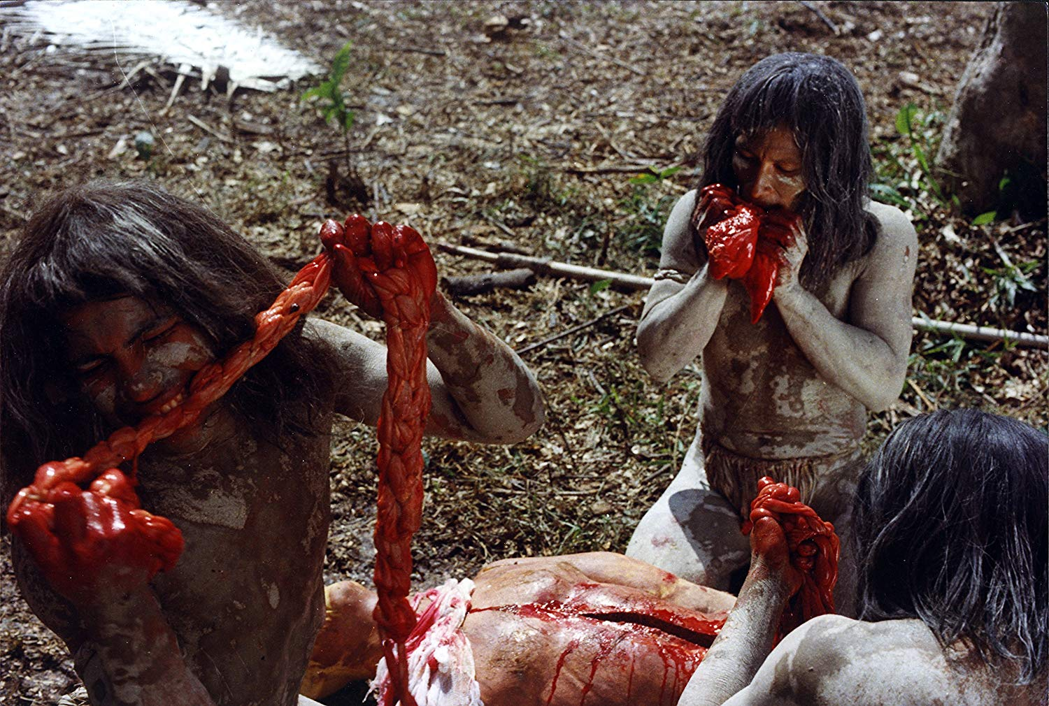 Natives munch on some intestines in Cannibal Ferox (1981)