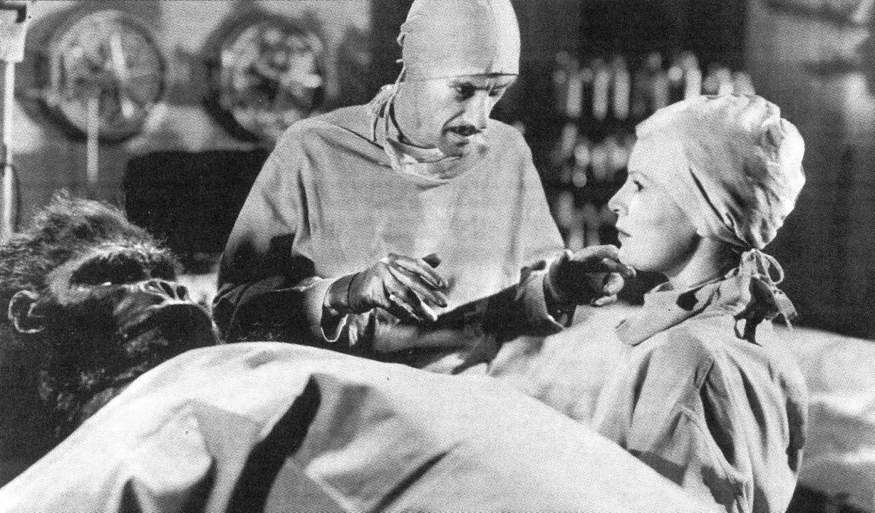 Mad scientist John Carradine about to deal with objections from nurse Fay Helm as he prepares to operate on the gorilla in Captive Wild Woman (1943)