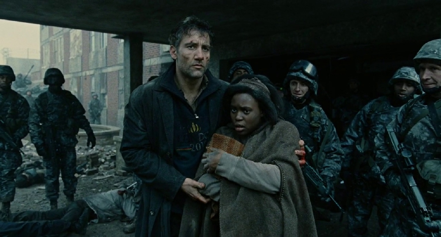 Clive Owen guides pregnant Claire-Hope Ashitey through the refugee camp in Children of Men (2006)