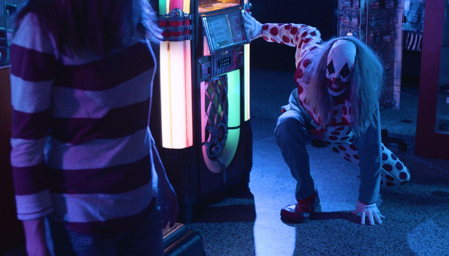 Brittany Belland pursued by Ribcage the clown (Eric Corbin) in Clowntergeist (2017)