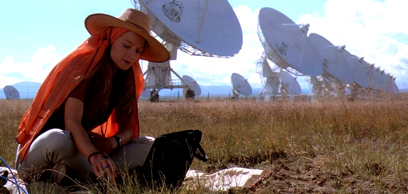 Ellie Arroway (Jodie Foster) listens to the stars in front of the Siccoro radio telescope array in Contact (1997)