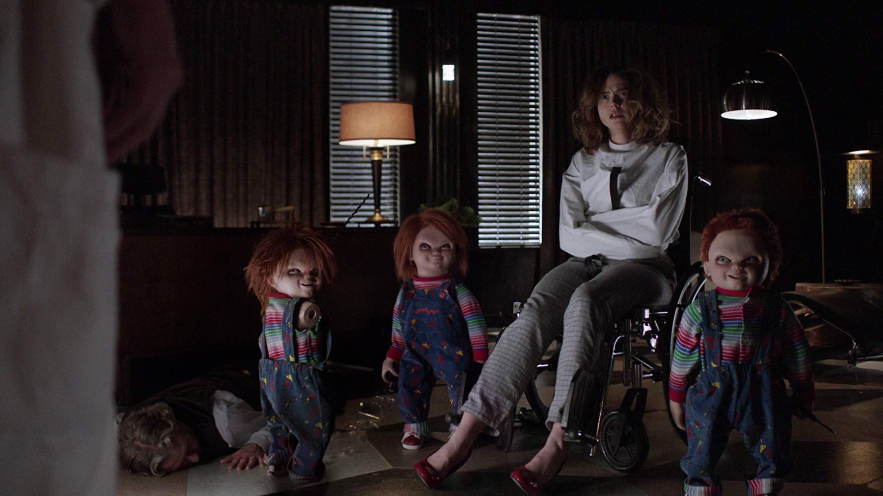 An incarcerated Fiona Dourif surrounded by Chucky dolls in Cult of Chucky (2017)