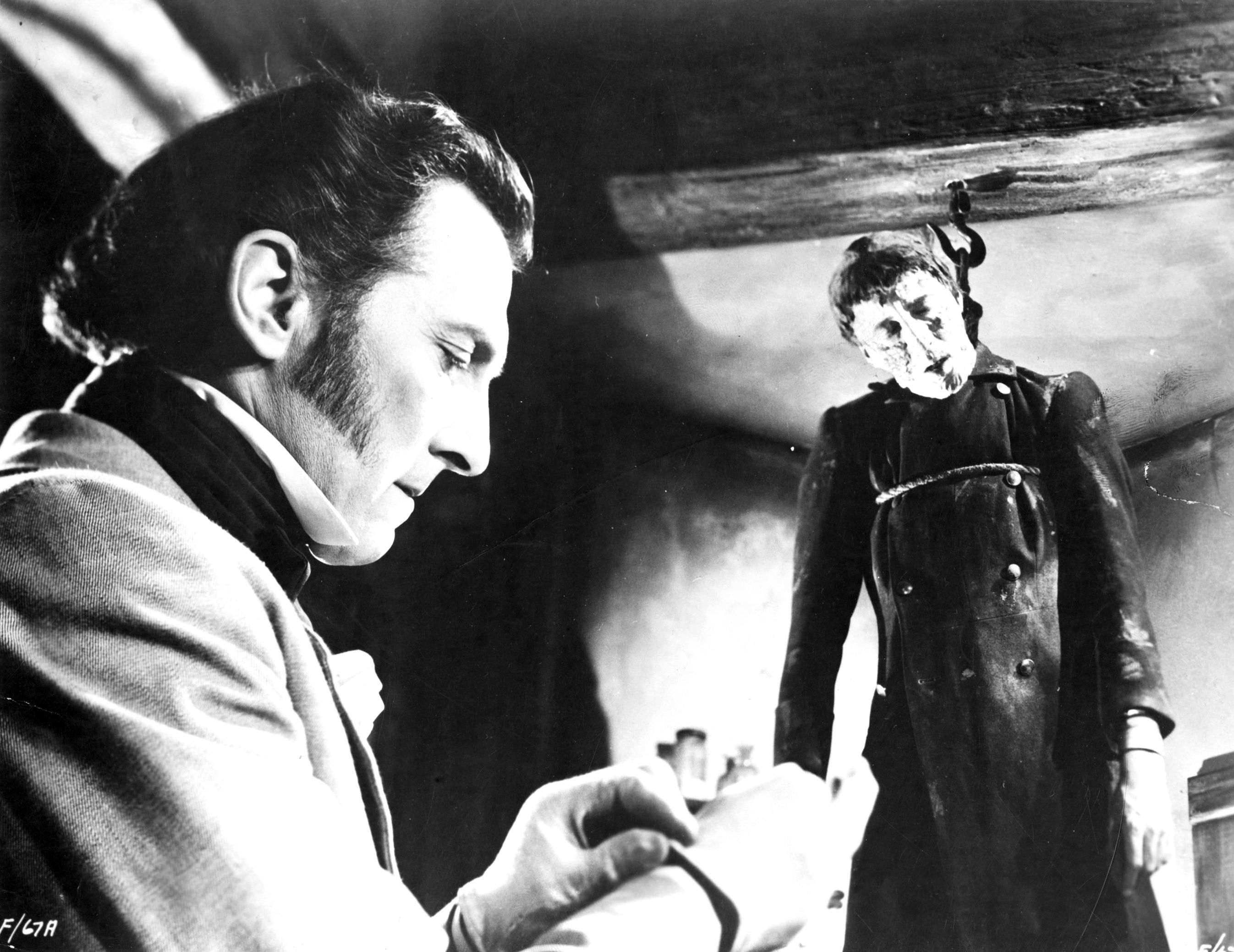 Baron Frankenstein (Peter Cushing) reads a book while his monster (Christopher Lee) hangs on a hook in The Curse of Frankenstein (1957)