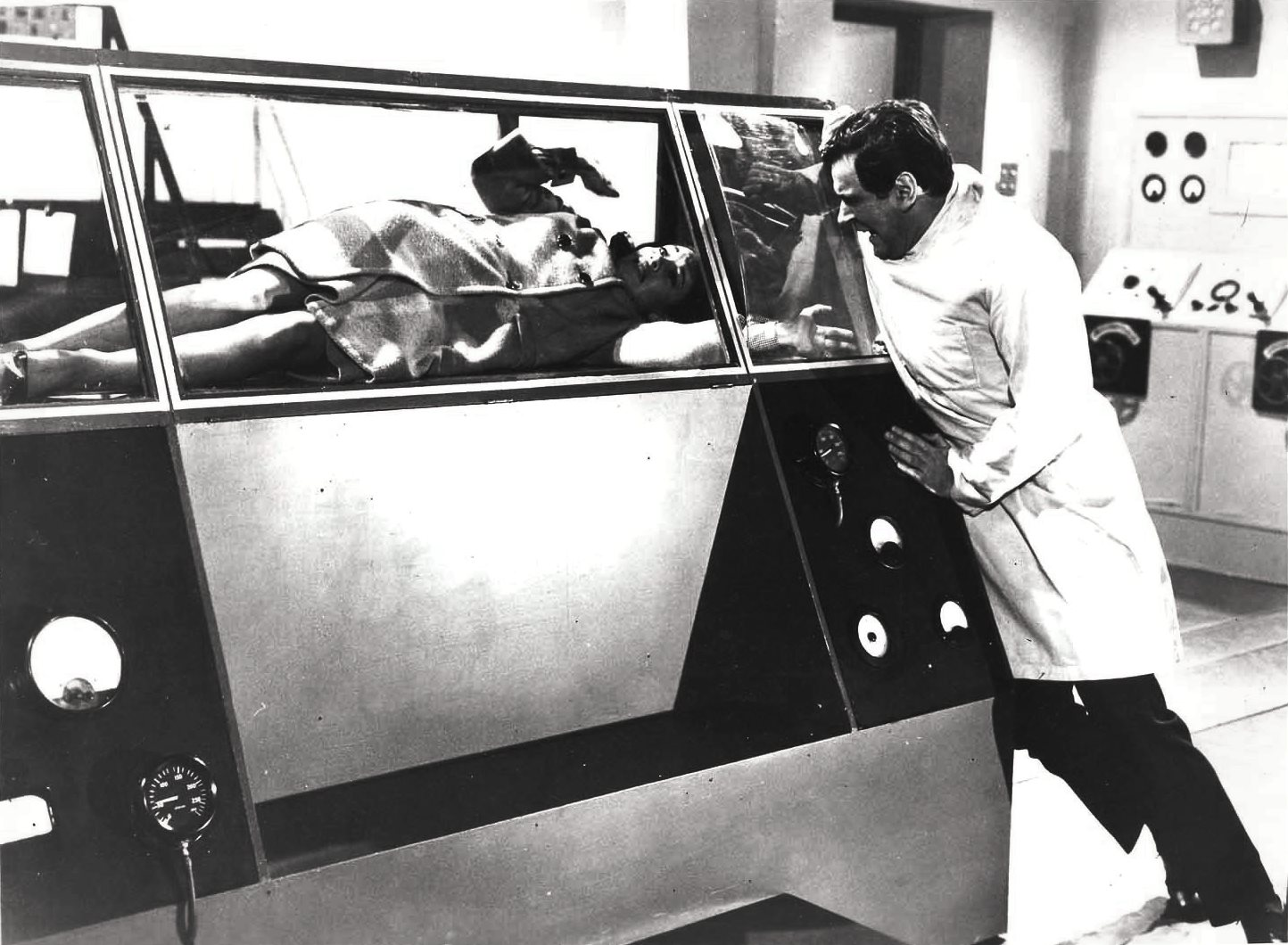 Carole Gray is trapped in the teleporter booth as Martin Delambre (George Baker) looks on in Curse of the Fly (1965)