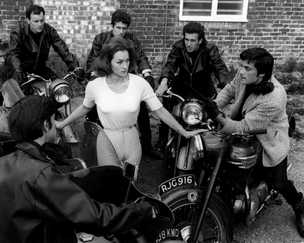 Shirley Ann Field surrounded by teddy boys with the leader King (Oliver Reed) on the right in The Damned (1963)
