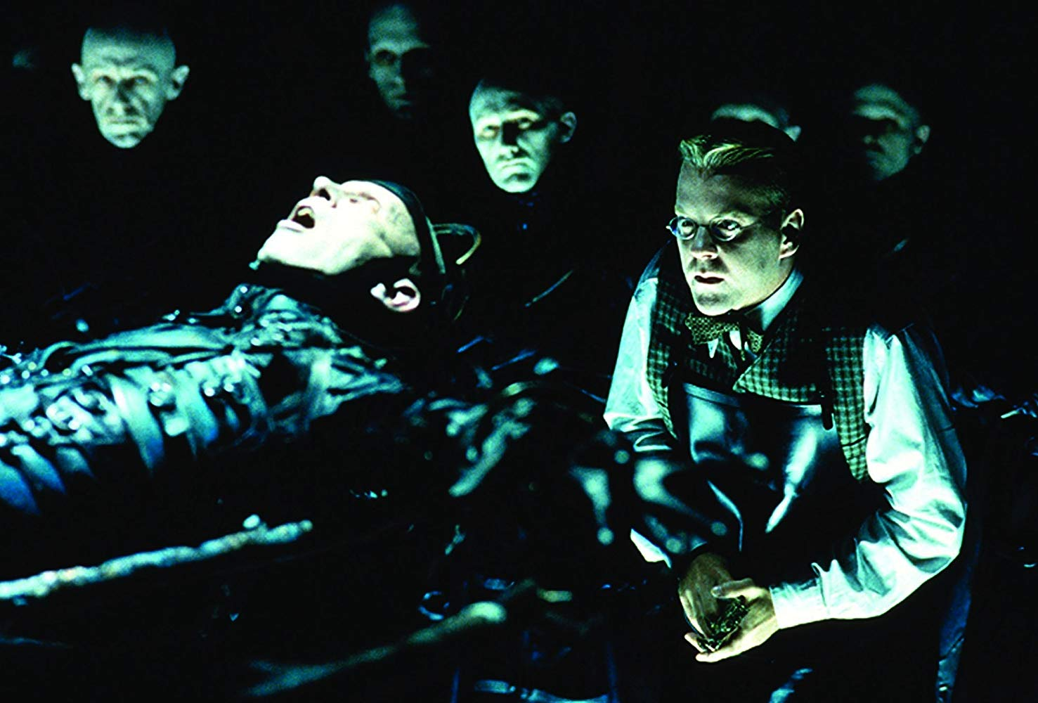 Kiefer Sutherland engaged in experiments surrounded by The Strangers in Dark City (1998)