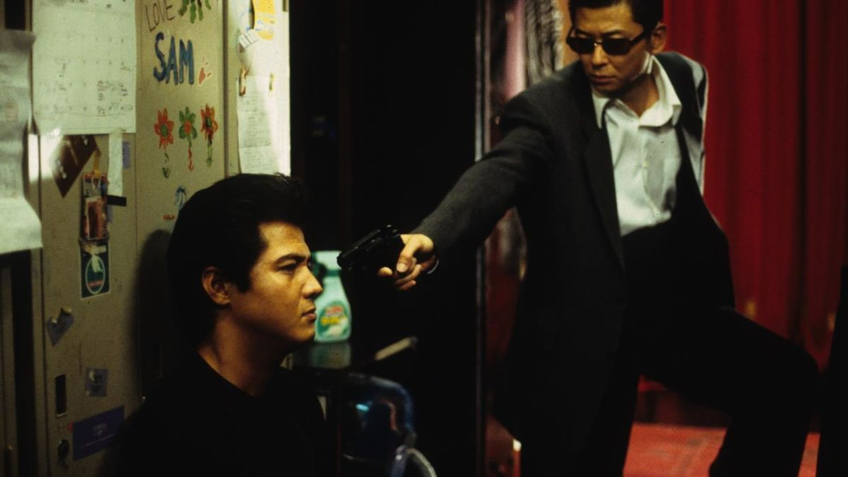 (l to r) Yakuza Riki Takeuchi has a gun held on him by detective Sho Aikawa in Dead or Alive (1999)