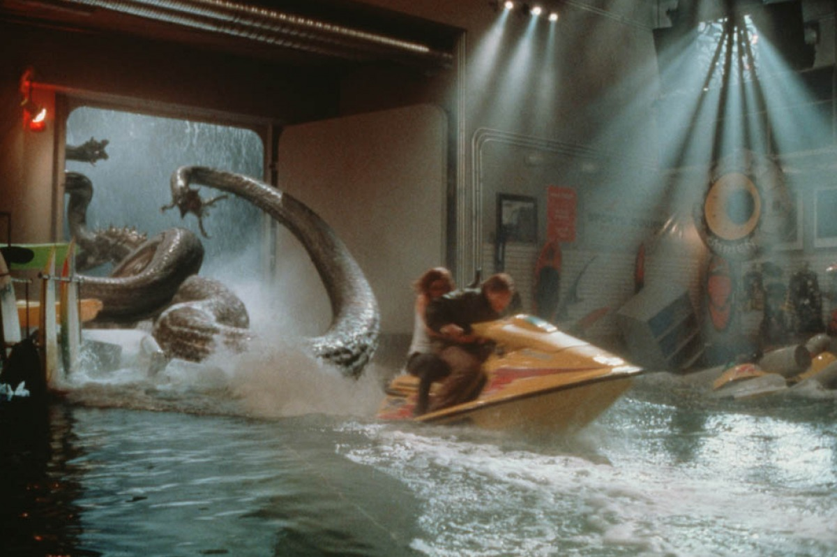 The creature pursues Famke Janssen and Treat Williams as they race through the ship by jetbike in Deep Rising (1998)