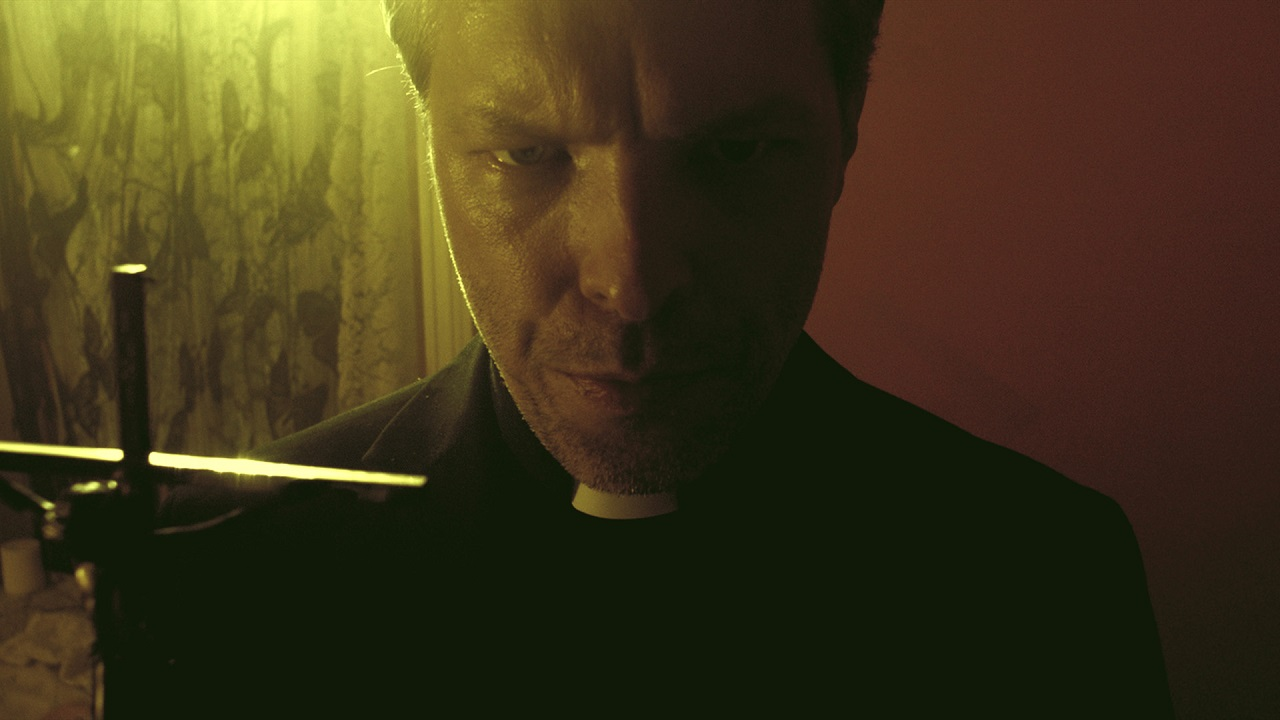 Miles Doleac (the film's director and lead actor) conducts an exorcism as a Catholic priest in Demons (2017)