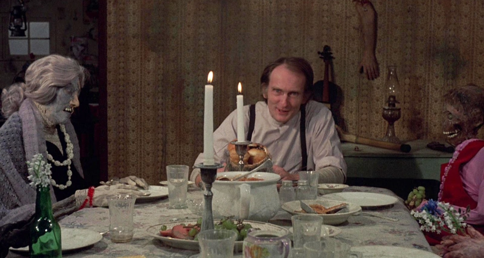 Roberts Blossom having dinner at a table of mummified corpses in Deranged (1974)